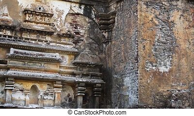 Intricately detailed relief sculpture on the exterior walls of an ancient ruin site near Polonnaruwa, Sri Lanka, depicts an ornate building. Video 1080p