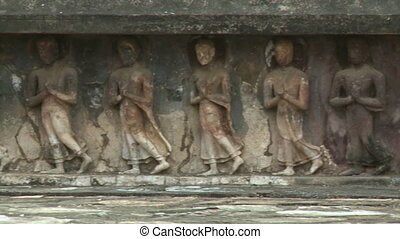 Numerous relief sculptures at the base of ancient religious building at Sukhothai Historical Park, depicting numerous Buddhist disciples walking with hands clasped