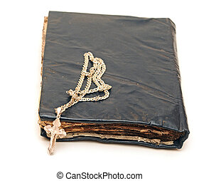 Religion. A cross with a chain against a old book