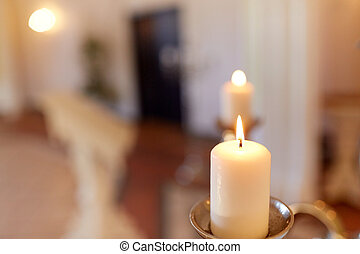 candles burning in church - religion and christianity...