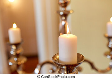 candles burning in church - religion concept - candles...