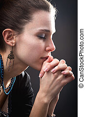 Religion concept - woman and her prayer over black