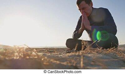 religion. Man praying sitting on the ground at sunset sun...