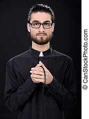 Religion - Praying priest. Portrait of priest standing...