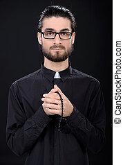 Religion - Praying priest. Portrait of priest standing...