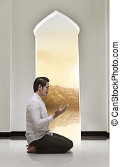 Religious asian muslim man kneeling and praying
