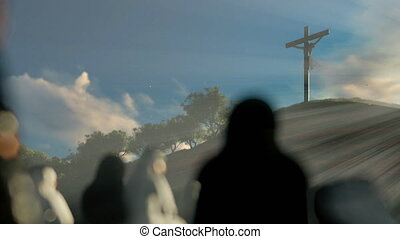Religious believers praying at Jesus cross at dawn