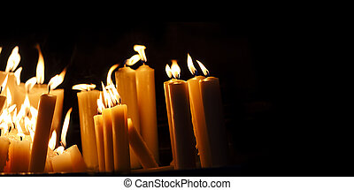 Religious candle light on black background. Yellow candlelight flame in dark christian church at night.