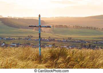 religious cross in the field. Cross on the background of the village.