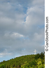 Religious cross on the mountain, between heaven and earth