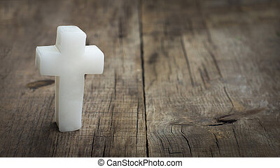 Religious cross out of wax on wooden textured background.