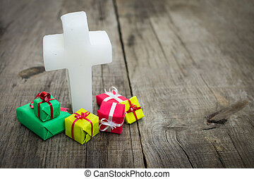 Religious cross with presents on wood background.
