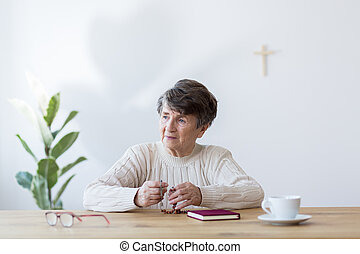 Religious elderly woman with rosary