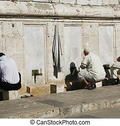 religious men washing feet near mosque