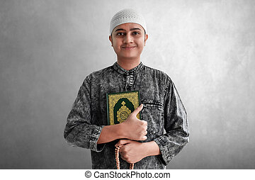 Religious muslim man holding quran and rosary beads
