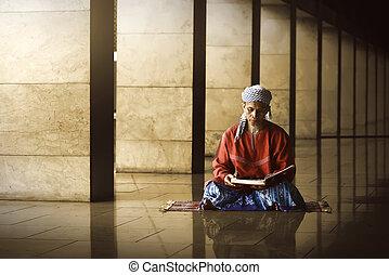 Religious muslim man reading holy koran inside the mosque