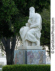 Large white religious statue of a saint in a graveyard
