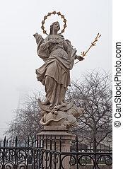 religious statue on plague pillar in Bratislava, New Bridge (SNP Bridge) visible in background.