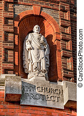 religious statue surrounded by ornate red brickwork