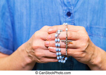 Religious woman with rosary close up