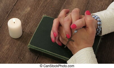 Religious woman with rosary keeping hands on Holy Bible