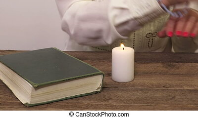 Religious woman with rosary set on fire candle near