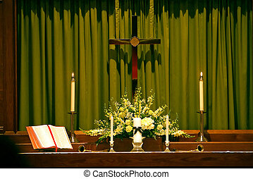 Religous altar that has a bible and candles on it with a cross hanging over it.