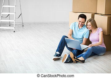 Relocating - Smiling attractive couple with laptop