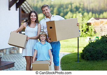 Relocation - Smiling family with boxes by the house