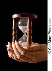 reloj de arena, fondo negro, manos