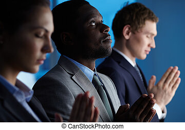Relying on Lord - Group of business partners praying for...