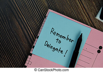 Remember to Delegate! write on sticky notes isolated on Wooden Table.