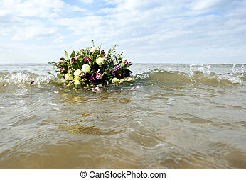 Bouquet afloat in the gentile surf of the north sea, as metaphor of remembrance of a watery grave