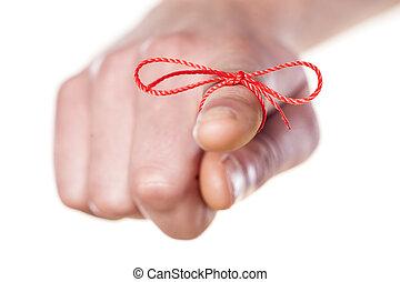 reminder - man's finger bound with red thread