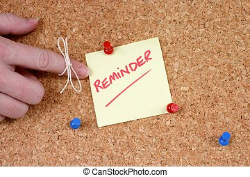 hand with string tied on finger pointing at reminder note pinned on corkboard