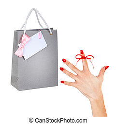 Reminder. Paper shopping bags and female hand with red ribbon on finger