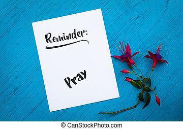 Reminder to Pray on white paper blue background