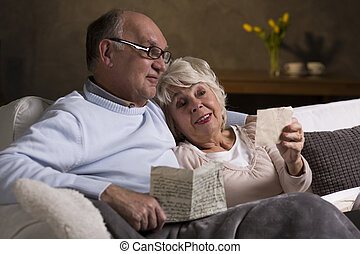 Reminding old times - Aged happy loving marriage reading old...