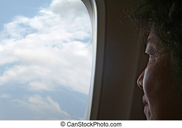 Reminiscing - An elderly Asian woman looking out the...