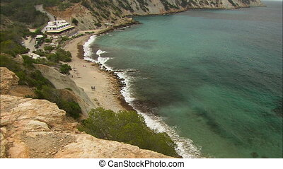 Medium low-angle panoramic still shot of a road leading to a remote resort close to a small beach line. Travellers stand at the sandy beach as waves from the green sea water slowly splash on eroded banks, Ibiza Island, Spain