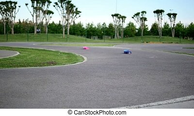 Remote control car racing on race track on a sunny day in...