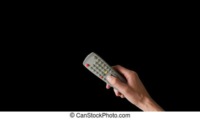 Remote control in hand, switches channels on TV