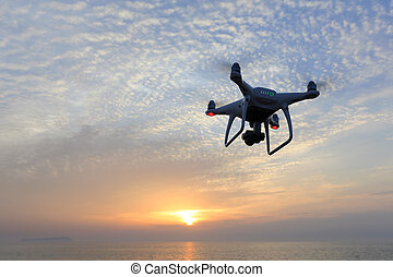 Remote controlled drone flying in air and sunset