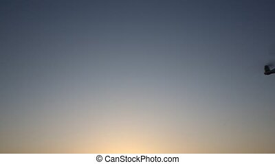 Remote controlled drone flying in the sunset sky - Remote...