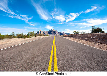 Remote desert road - A remote and deserted desert road with...
