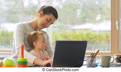 mother with baby working on laptop at home office - remote ...