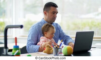 father with baby working on laptop at home office - remote ...
