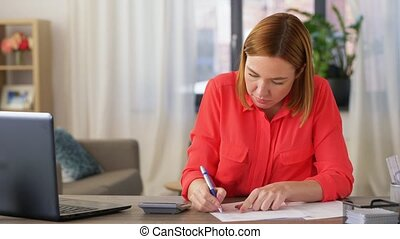woman with calculator and papers working at home - remote ...