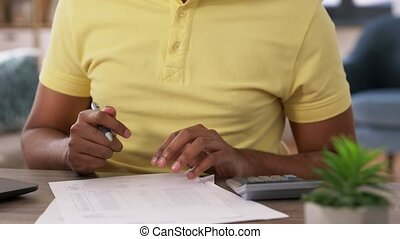 man with calculator and papers working at home - remote job...
