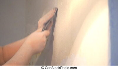 Removes old plaster from wall with a scraper - Removes old...